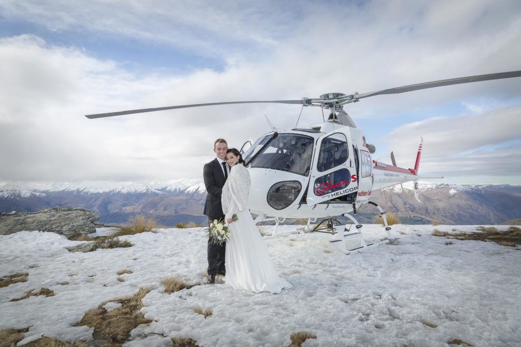 Couple by Helicopter in Snow on Mountain