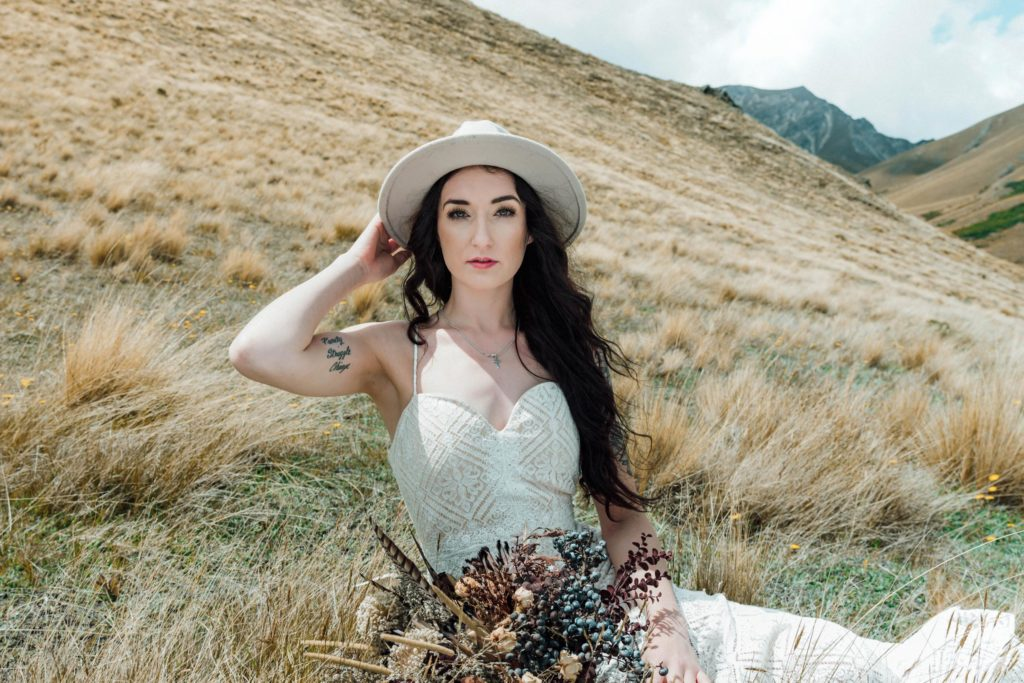 Bride sitting in grass by tussocks