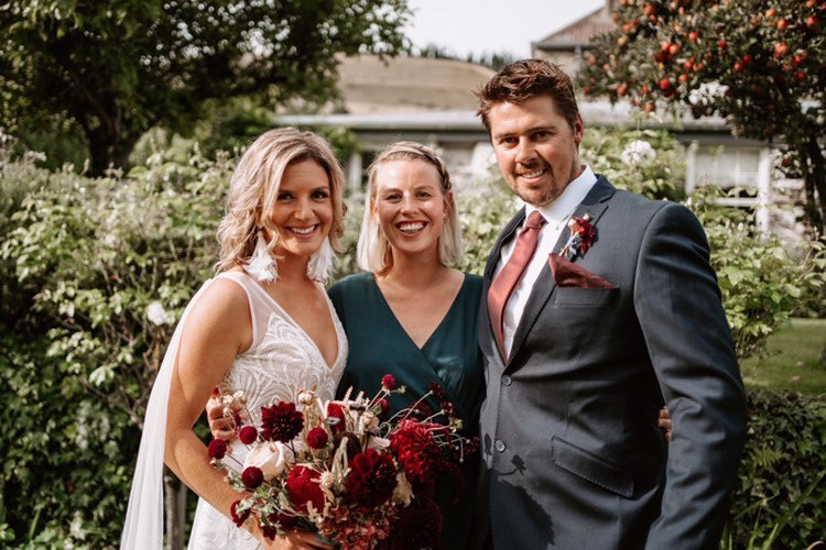Bride and groom pose for a photo with their wedding celebrant in Cromwell Queenstown