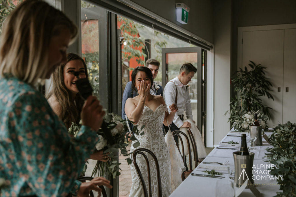Wedding reception speeches with MC and bride laughing