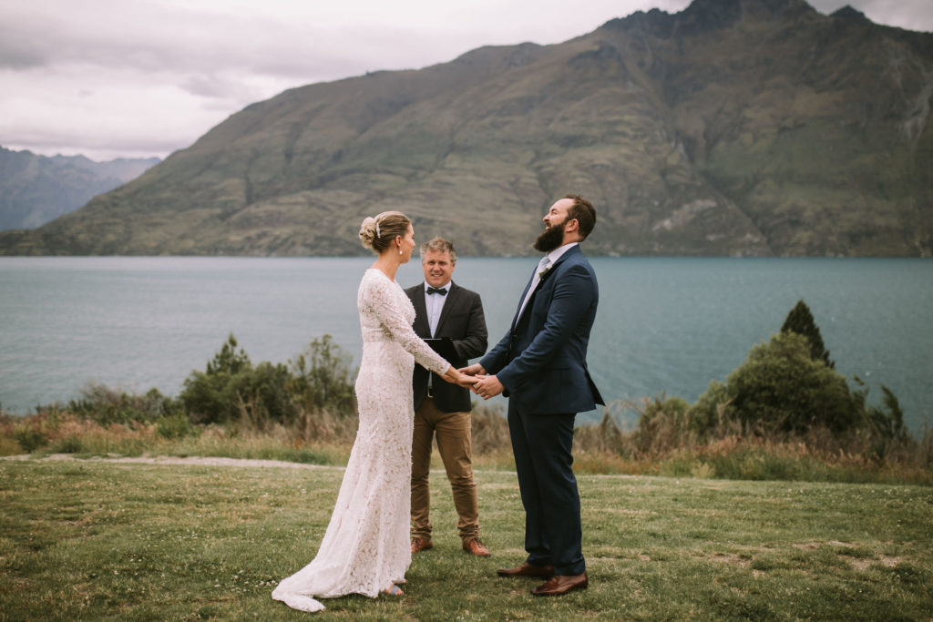 Wedding ceremony in Queenstown New Zealand with bride groom and celebrant laughing