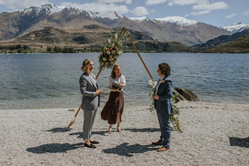 Wedding ceremony by the lake in Wanaka New Zealand with two brides and their celebrant