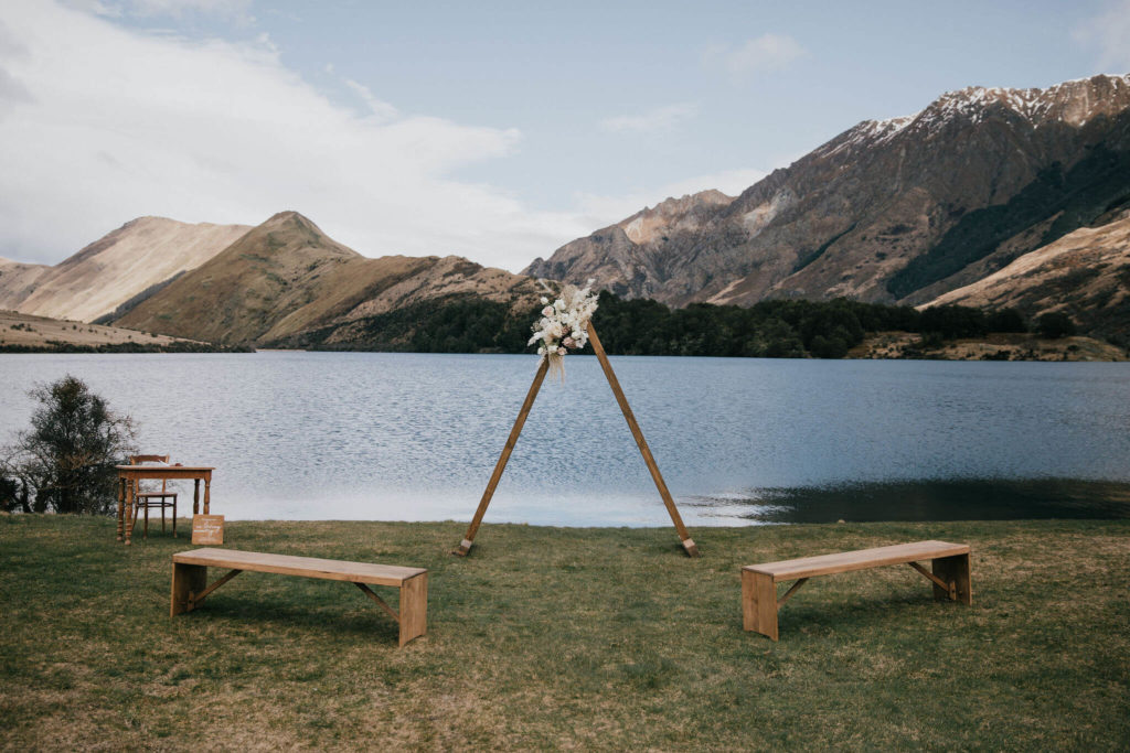 Wedding ceremony setup at Moke Lake, Queenstown, with triangle arch and two bench seats