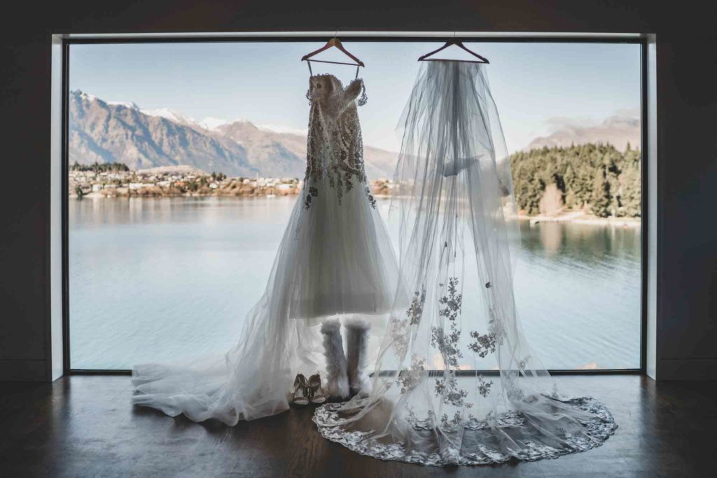 Elly and Sam Bridal Dress Hung by Window